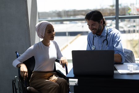 Front view of disabled young mixed-race woman and handsome Caucasianmale doctor interacting with each other in hospital