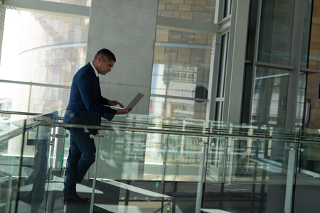 Side view of a handsome businessman working on his laptop on the first floor walkway of the office against pillar in background