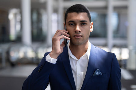 Front view of handsome young mixed-race businessman looking at camera while using mobile phone in modern office