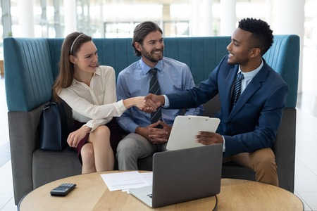 Front view of young multi-ethnic business people shaking hands with each other in the lobby at office Stock Photo