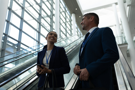 Low angle view of mixed-race businessman and businesswoman interacting with each other near escalator in office