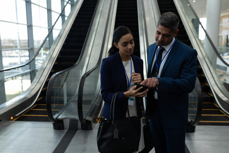 Front view of mixed-race businessman and businesswoman discussing over mobile phone near escalator in office Banco de Imagens