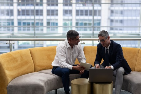 Front view of mature Caucasians business executives talking discussing over laptop while sitting on the sofa in modern office Stock Photo