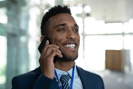 Front view of happy mixed-race businessman talking on mobile phone in the modern corridor at office. He is smiling Stock Photo