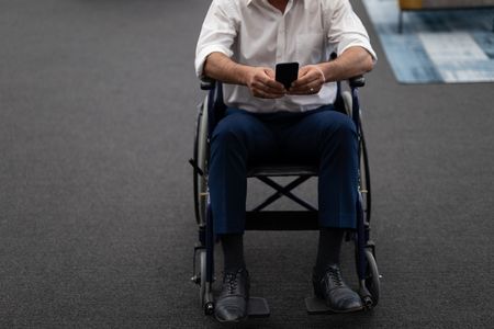 Low section of mature Caucasian disabled businessman using mobile phone while sitting on wheelchair in modern office