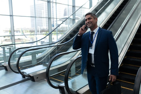 Front view of Caucasian businessman talking on mobile phone while moving down on escalator in office lobby Stock Photo