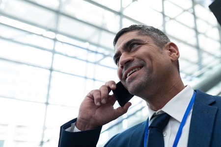 Close-up of Caucasian businessman talking on mobile phone in escalator Stock Photo - 121913237