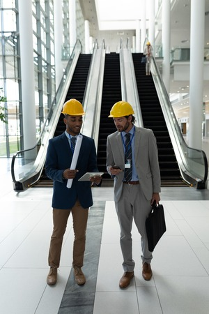 Front view of young multi-ethnic male architect discussing over digital tablet standing in office lobby Imagens
