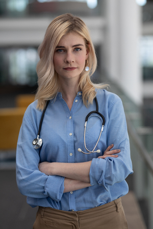 Portrait of beautiful young blonde Caucasian female doctor with arms crossed looking at camera in clinic