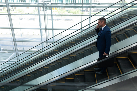 Side view of Caucasian businessman talking on mobile phone while moving down on escalator in office