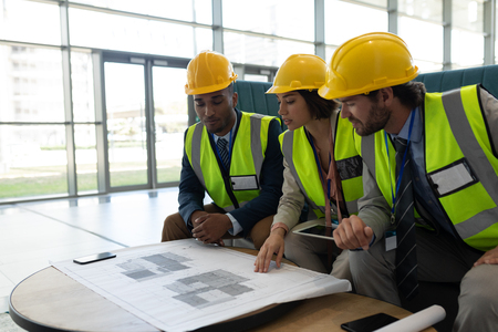 Side view of young multi-ethnic business architect sitting and discussing over the blue print in lobby at office. They wear safety helmets Stock fotó - 122221541