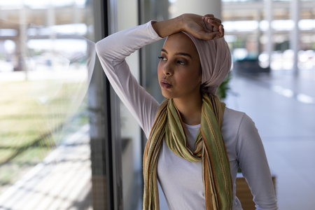 Front view of beautiful young mixed-race female executive looking through window standing in modern office 免版税图像