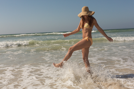 Side view of beautiful young Caucasian woman in bikini and hat kicking wave in the waves by ocean. She is smiling Stock Photo