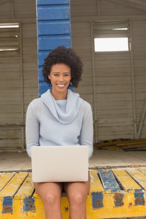 Portrait of happy young African American woman using her laptop on the beach hut. She is looking ans smiling at camera