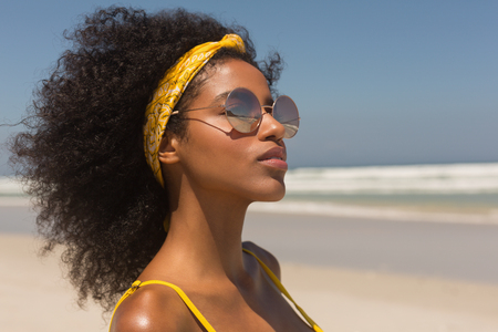 Side view of pretty young African American woman in yellow bikini and sunglasses standing on the beach in the sunshine. She is smiling Foto de archivo