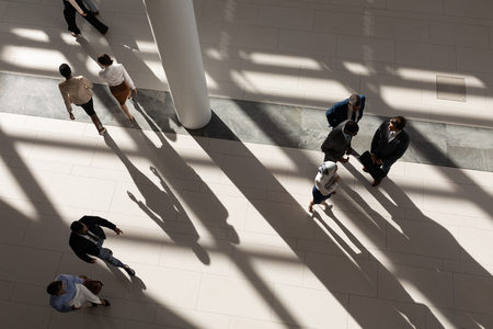 High angle view of multi-ethnic business executives standing in lobby at office
