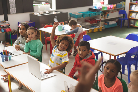 Front view of row of school kids listening their teacher and one of them raising his finger to answer a question in classroom at school