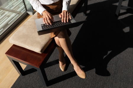 Low section of young Caucasian businesswoman using digital tablet while sitting on bench in modern office