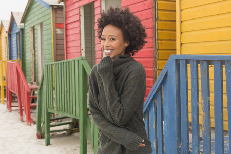 Front view of pretty happy young African American woman standing at beach hut. She is smiling Stock fotó