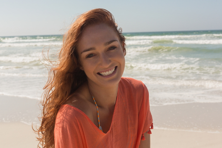 Front view of beautiful happy young Caucasian woman looking at camera on the beach. She is smiling Foto de archivo