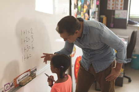 Side view of a Caucasian teacher learning mathematics to a mixed-race school girl on a whiteboard against drawing on wall in background