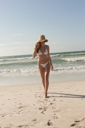 Front view of gorgeous young Caucasian woman in hat and bikini walking on the beach. It is sunny day