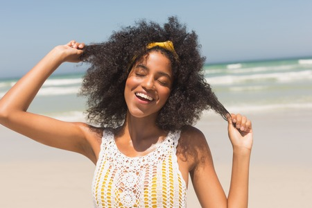 Front view of happy young African American woman with eyes closed playing with hair standing on the beach. She is smiling Banco de Imagens