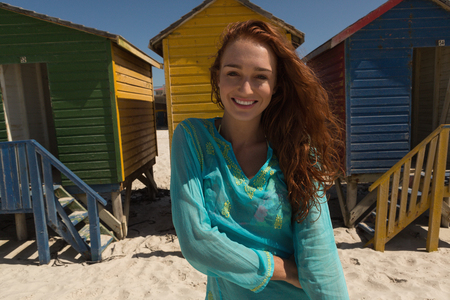 Portrait of happy gorgeous young Caucasian woman looking at camera standing on the beach. She is smiling and enjoying at camera