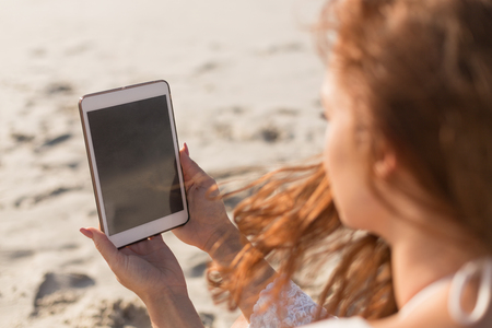 Side view of beautiful young Caucasian woman using digital tablet sitting on the beach. It is sunny day Stock Photo