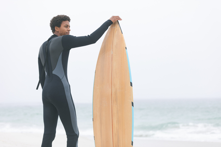 Rear view of thoughtful young mixed-race male surfer holding surfboard on the beach. He is looking away