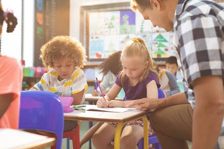 Vista lateral de un maestro interactuando con la niña de la escuela mientras está sentado en el aula en la escuela