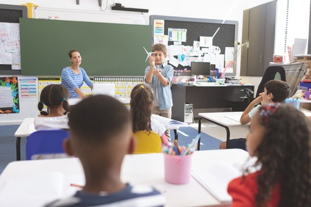 Front view of schoolboy explaining  to his classmates about windmill in classroom while her teacher looking at him Stock Photo