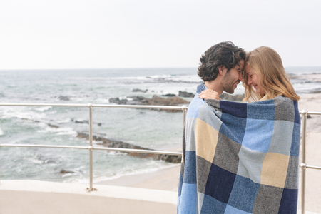 Side view of happy young Caucasian couple wrapped in blanket standing at promenade near beach om a sunny day. They are smiling