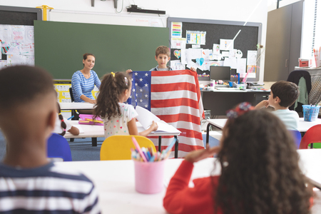Front view of a schoolboy holding an american flag in classroom at school with his classmates in foreground Foto de archivo