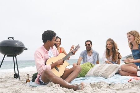 Front view of african american man playing guitar while friends enjoying on beach while having beer Standard-Bild