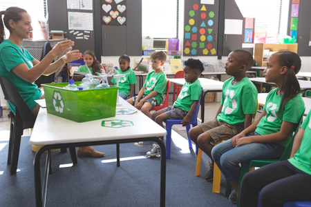 Side view of teacher interacting with school kids about green energy and recycle at desk in classroomat school