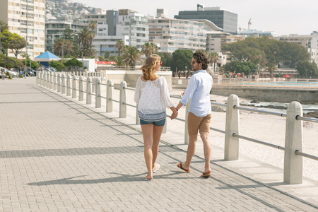 Rear view of young Caucasian couple walking hand in hand on the promenade at the seaside