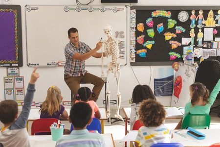 Front view of teacher explaining about human skeleton in classroom at school with school kids sitting on their colored chairs in foreground