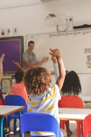 Rear view of school kids raising hand to answer at a question while the teacher speaking at whiteboard