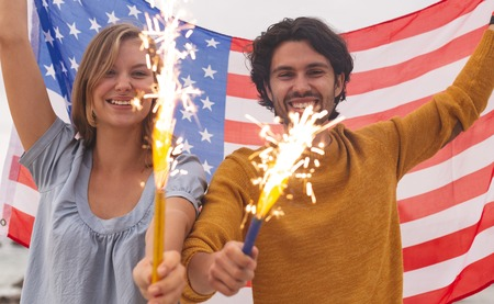 Portrait of young Caucasian couple playing with fire cracker while holding american flag. They are smiling and looking at camera