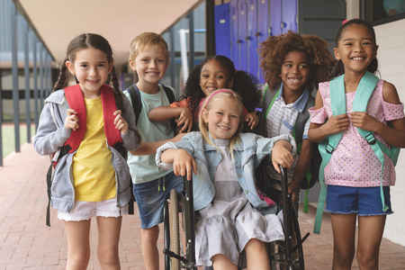 Front view  of happy school kids standing in  outside corridor at school while a Caucasian schoolgirl is sitting on wheelchair in foreground Banco de Imagens