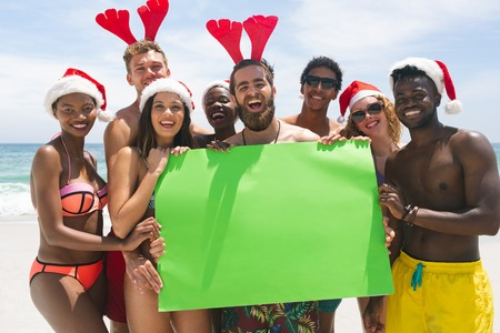Front view of happy multi-ethnic group of friends holding a empty green placard at beach on a sunny day. The are smiling and looking at camera