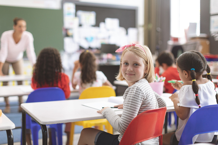 Rear view of a Caucasian schoolgirl looking at the camera and sitting on a red chair next to her classmate sitting on a blue chair against her teacher in background