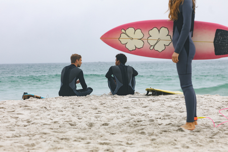 Rear view of multi ethnic male friends interacting with each other while woman standing with surfboard on beach Stock Photo