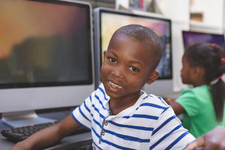 Portrait of happy African-american schoolboy sitting and looking at camerain computer room