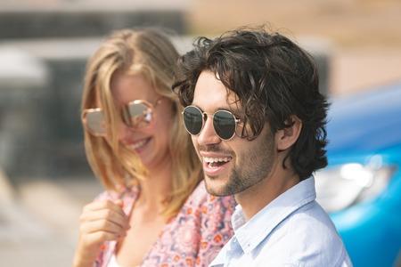 Widok z boku szczęśliwa młoda para Kaukaski z okulary stojące na promenadzie w słoneczny dzień. Oni się uśmiechają