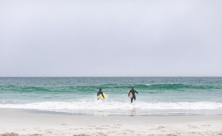 Front view of young multi-ethnic male friends running on beach while holding surfboards