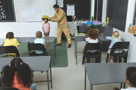 Overhead view of firefighter teaching student about fire safety in classroom at school Imagens