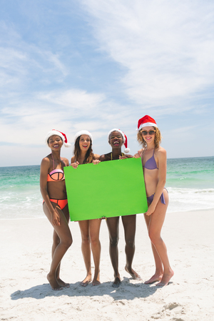 Portrait of happy multi-ethinic female friends with Christmas hat holding a empty green placard at beach on a sunny day. They are smiling and looking at camera