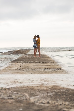 Side view of young Caucasian couple kissing each other standing on rock with arm around near beach
